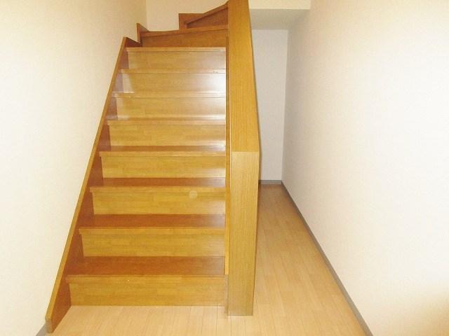 室内に階段がございます。細い通路の奥には階段下収納があります。